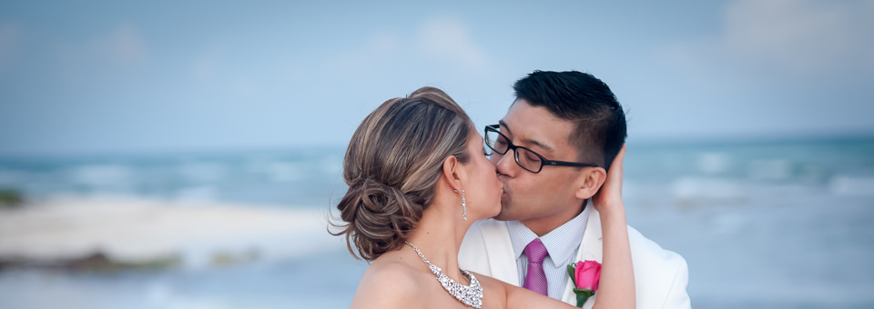 bride and groom kiss against backdrop of the sea, photographed by Cancun wedding photographer, dorota jamal