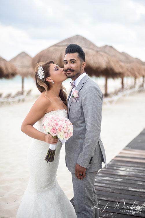 Bride kissing groom in Cancun beach