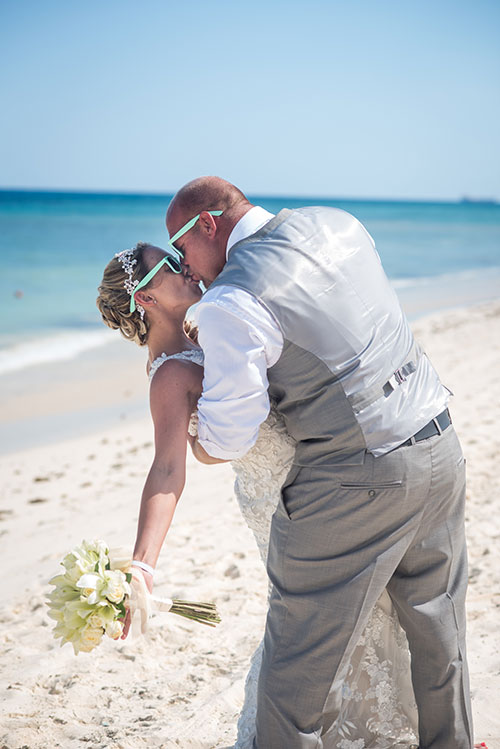 Bride and groom kissing in beach wedding
