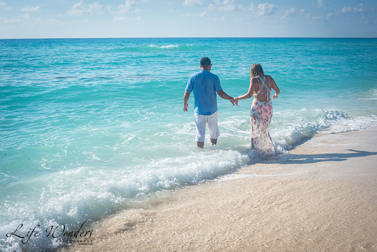 couple playing in the water on cancun beach