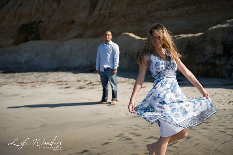 woman dancing on the shore for her engagement photo - marriage proposals