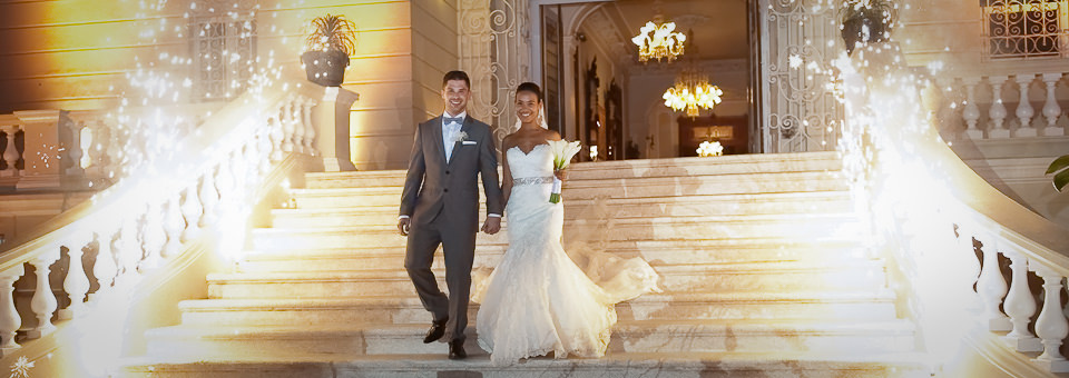 wide shot of groom and bride walking down steps