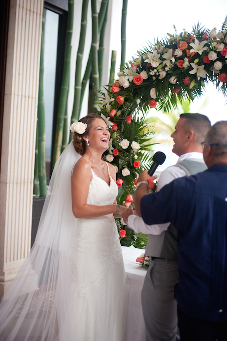 bride & groom share laughter during their vows - photographed by Riu Palace Resort wedding photographer