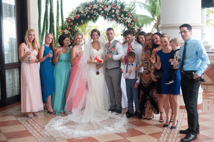newlyweds and guests pose for group photo - taken by Riu Palace Resort wedding photographer - Riu Cancun Wedding