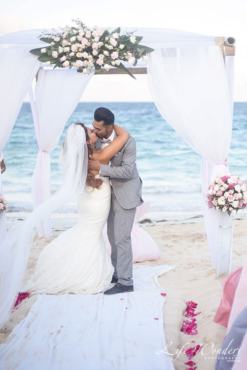 Bride and groom first kiss in Cancun beach