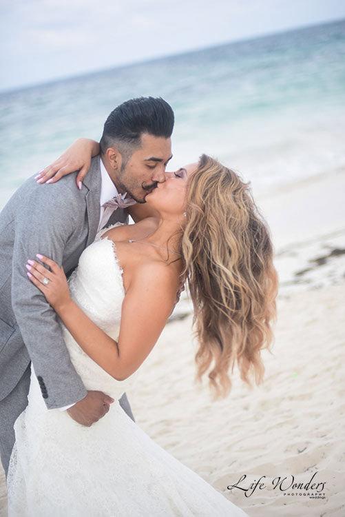 bride and groom kiss in beach wedding
