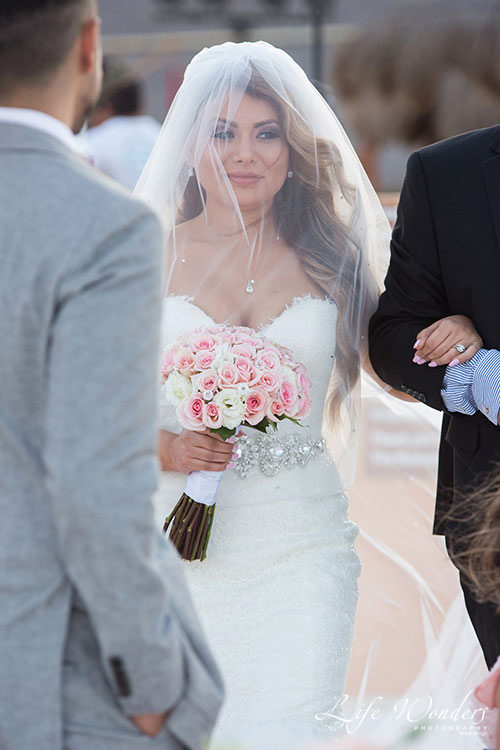 Bride arriving to beach wedding ceremony