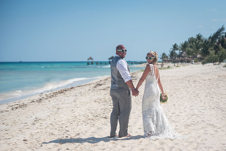 Bride and groom wearing sunglasses in the beach