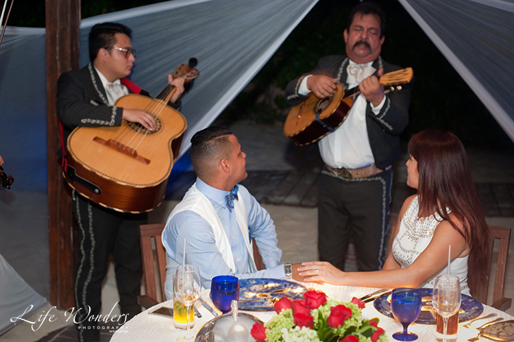 couple listening to mariachi band player