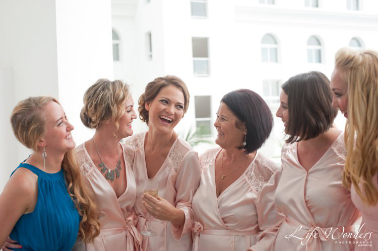 bride smiling with bridesmaids getting ready