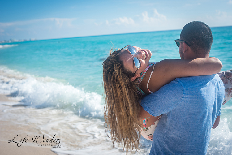 man carrying woman on cancun beach