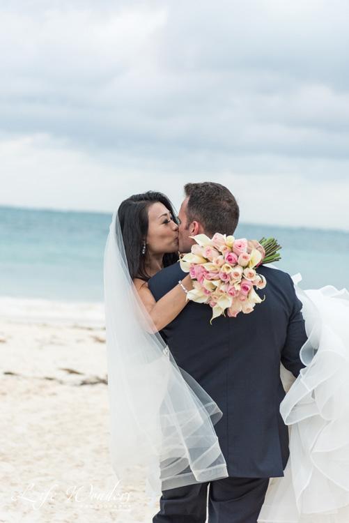 Groom holding bride kissing