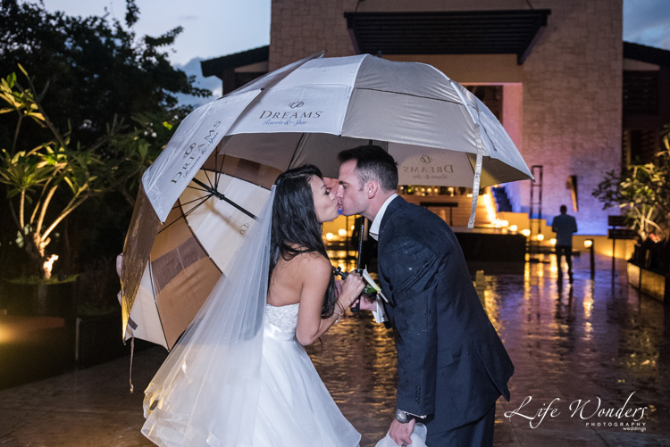 bride kissing umbrella rain on wedding day in riviera maya