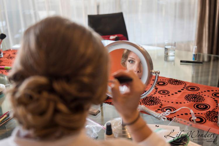 wedding photographer bride getting makeup ready