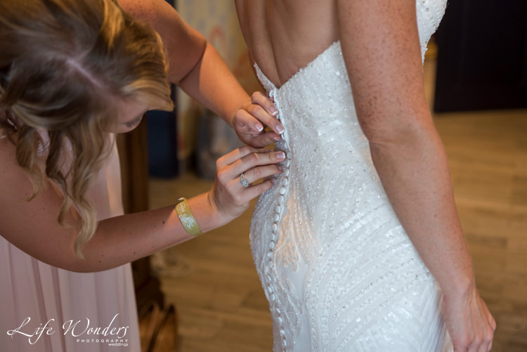 playa del carmen wedding photographer bridesmaid helping beautiful bride dressing