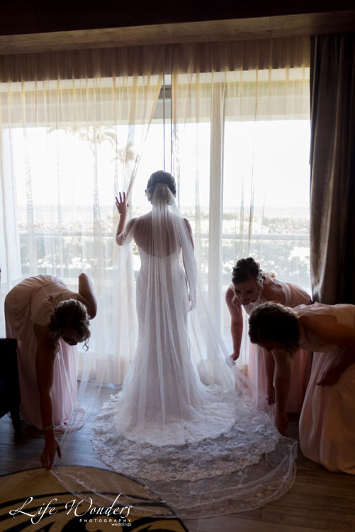 playa del carmen wedding photographer bridemaids helping bride with her white dress