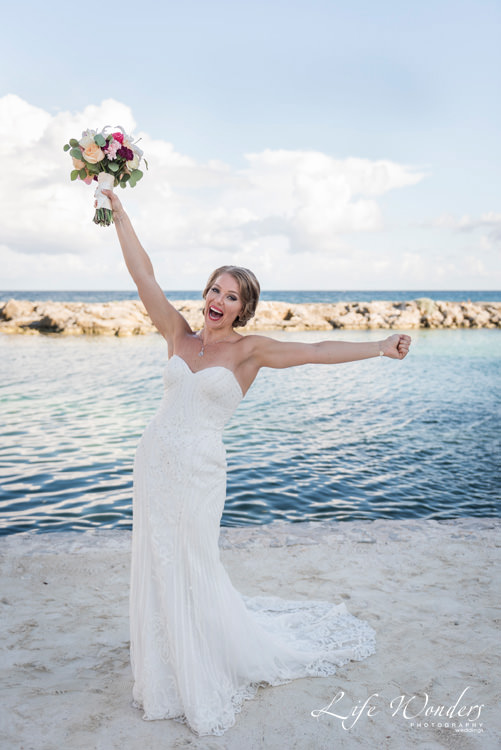 beautiful happy bride holding wedding bouquet up high