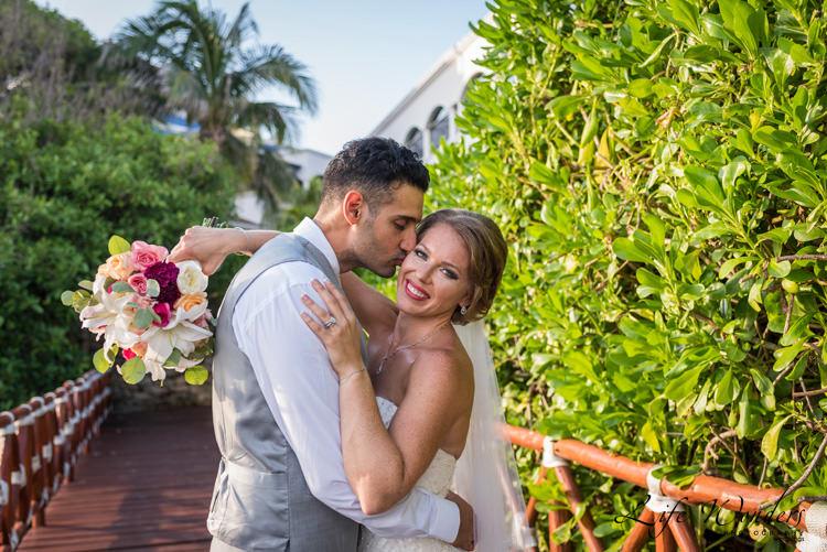groom kissing smiling bride on the cheek