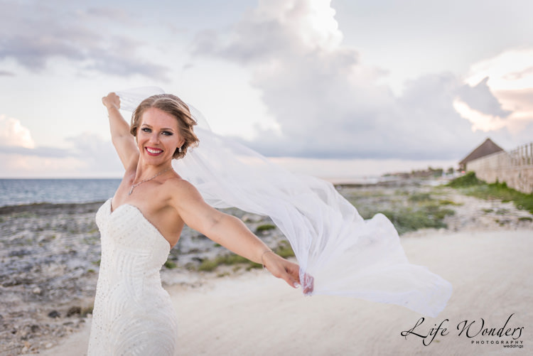 smiling bride with her wedding veil flying