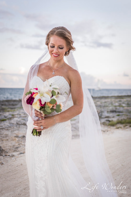 beautiful bride in white wedding dress holding colorful bouquet