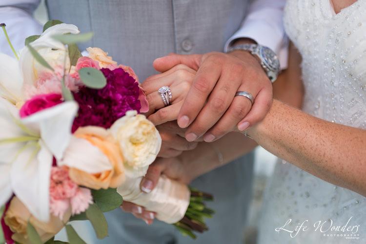 bride groom showing their wedding rings