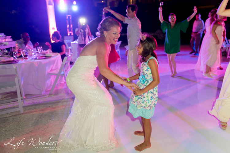 smiling bride dancing with a young girl