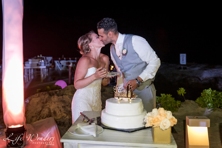 groom kissing bride in front of wedding cake