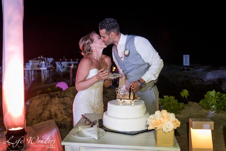 groom kissing bride in front of wedding cake